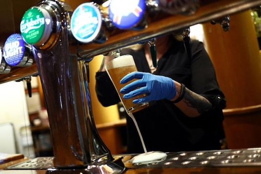 A worker serves a beer at The Holland Tringham Wetherspoons pub after it reopened following the outbreak of the coronavirus disease (COVID-19), in London, Britain July 4, 2020. REUTERS/Hannah McKay