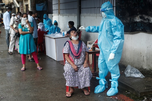 A healthcare worker collects a swab sample from a woman during a medical campaign for the coronavirus disease (COVID-19), in Mumbai, India, July 4, 2020. (REUTERS)