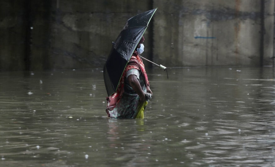 A woman wearing a mask as a precaution against the coronavirus walks through a waterlogged street during monsoon rains in Mumbai, India, Sunday, July 5, 2020. India's monsoon season runs from June to September. (AP Photo/Rafiq Maqbool)
