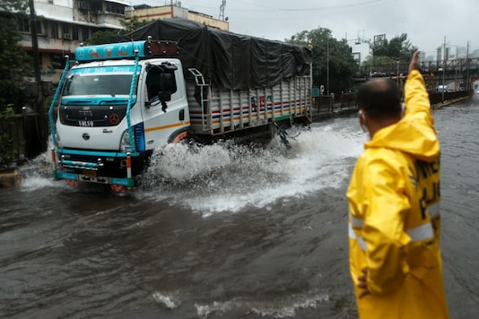 A municipal worker directs traffic on a waterlogged road during heavy rains in Mumbai. (Image: Reuters)