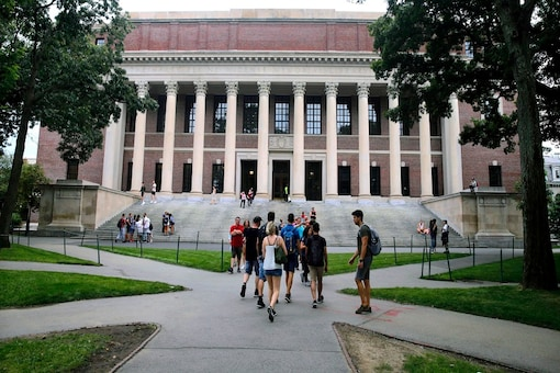 Students walk near the Widener Library in Harvard Yard at Harvard University in Cambridge. The Ivy League school announced Monday, July 6, 2020, that as the coronavirus pandemic continues its freshman class will be invited to live on campus this fall, while most other undergraduates will be required learn remotely from home. (AP Photo/Charles Krupa, File)