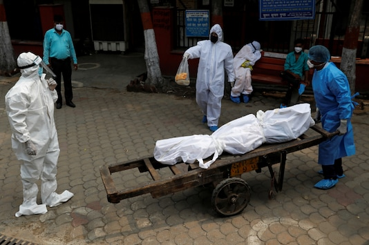 A health worker wearing Personal Protective Equipment (PPE) carries the body of a person who died due to the coronavirus disease (COVID-19), on a handcart at a crematorium in New Delhi, India, July 6, 2020. REUTERS/Anushree Fadnavis
