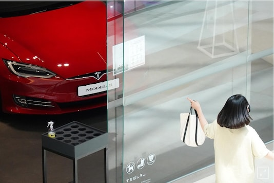 A woman walks past a Tesla dealership in Hanam, South Korea. (Image Source: Reuters)