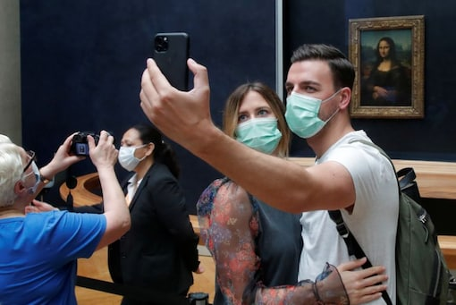 """Visitors, wearing protective face masks, make a selfie in front of the """"Mona Lisa"""" (La Joconde) by Leonardo Da Vinci at the Louvre museum in Paris as the museum reopens its doors to the public after almost 4-month closure due to the coronavirus disease (COVID-19) outbreak in France. (Image: Reuters)"""