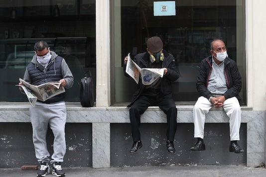 People wearing masks to curb the spread of the new coronavirus wait for businesses to open in downtown Lima, Peru. (AP Photo/Martin Mejia)