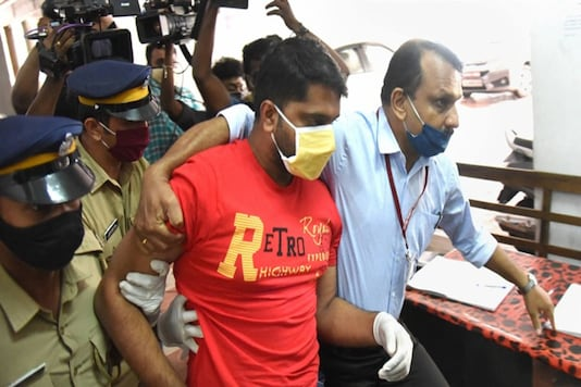 Police personnel produce Sarith, an accused in the gold smuggling case, at a special court in Kochi on Thursday. (PTI)