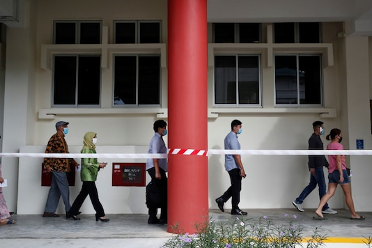 Singapore's President Halimah Yacob (in green) and her husband join a queue of voters wearing face masks at a polling station during the general election, amid the coronavirus disease (COVID-19) outbreak, in Singapore July 10, 2020. REUTERS/Edgar Su