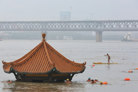 FILE PHOTO: People swim near a pavilion partially submerged in floodwaters on the banks of the Yangtze River, following heavy rainfall in Wuhan, Hubei province, China July 8, 2020. China Daily via REUTERS/File photo
