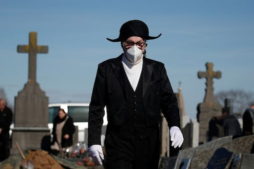For representation only: A member of the Charitable Brotherhood of Saint-Eloi de Bethune, which first formed during the plague 800 years ago, wears a protective face mask as he walks in the cemetery during a burial ceremony in Bethune, France, March 18, 2020. Funeral gatherings are restricted because of the coronavirus disease (COVID-19) outbreak. Picture taken March 18, 2020. REUTERS/Pascal Rossignol