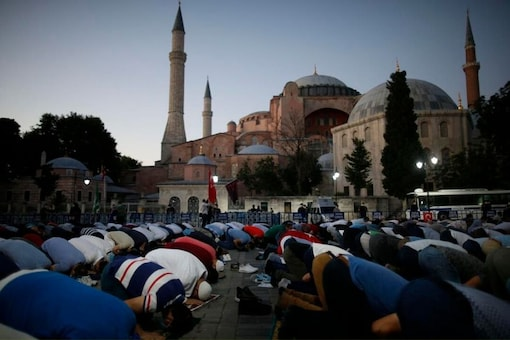 Muslims offer their evening prayers outside the Byzantine-era Hagia Sophia, one of Istanbul's main tourist attractions in the historic Sultanahmet district of Istanbul, following Turkey's Council of State's decision, Friday, July 10, 2020. (AP Photo/Emrah Gurel)