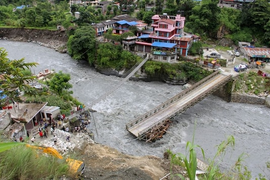 People gather near the bridge that is damaged due to the flood at Raghu Ganga River in Myagdi, Nepal July 11, 2020. REUTERS/Santosh Gautam