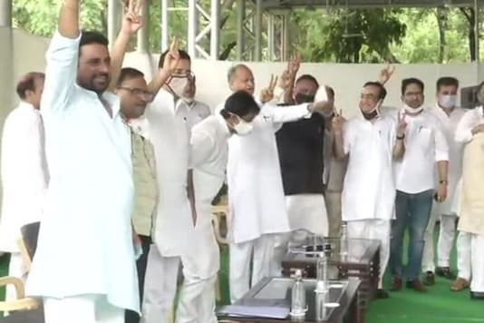 Chief Minister Ashok Gehlot, Congress leaders and party MLAs show victory sign, as they gather at CM's residence in Jaipur. (ANI)