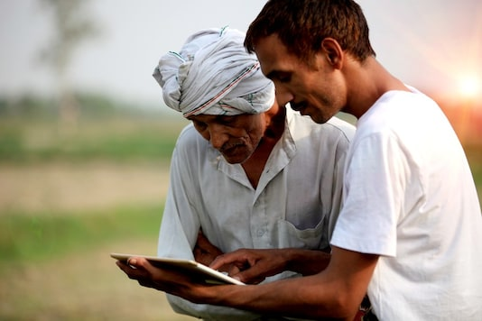 A man guides an acquaintance in using a smart hardware interface in India. (Image: iStock/WEF)