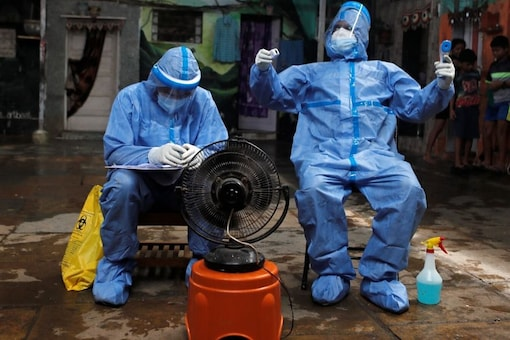 File photo of healthcare workers resting in front of a fan during a check up campaign for the coronavirus disease (COVID-19). (Reuters)