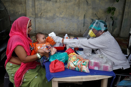 FILE PHOTO: A doctor wearing a protective face shield uses an infrared thermometer to measure the temperature of a child in Ahmedabad, India, June 15, 2020. REUTERS/Amit Dave/File Photo