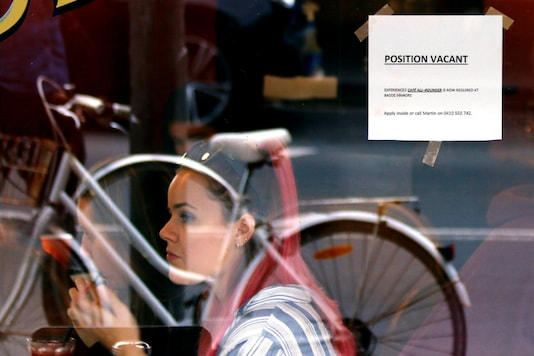 Customers at a local cafe are seen through a window displaying a job vacancy notice in central Sydney, Australia, May 9, 2016. Picture taken May 9, 2016. REUTERS/Steven Saphore/Files