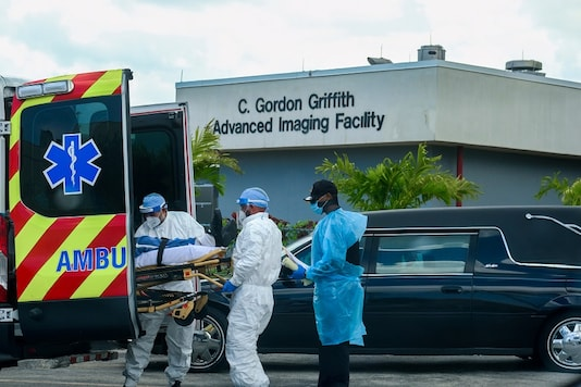 Emergency Medical Technicians (EMT) arrive with a patient while a funeral car begins to depart at North Shore Medical Center where the coronavirus disease (COVID-19) patients are treated, in Miami, Florida, US July 14, 2020. (REUTERS/Maria Alejandra Cardona)