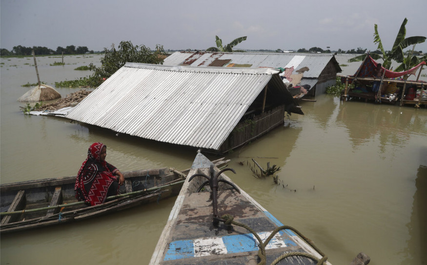 An Indian flood affected woman sits on a country boat near her submerged house in Gagolmari village, Morigaon district, Assam, India, Tuesday, July 14, 2020. Hundreds of thousands of people have been affected by floodwaters and landslides following incessant rainfall in the region. (AP Photo/Anupam Nath)