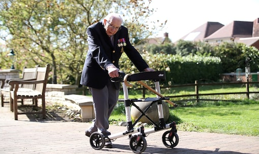FILE PHOTO: Retired British Army Captain Tom Moore, 99, walks to raise money for health workers, by attempting to walk the length of his garden one hundred times before his 100th birthday this month as the spread of coronavirus disease (COVID-19) continues, Marston Moretaine, Britain, April 15, 2020. REUTERS/Peter Cziborra/File Photo