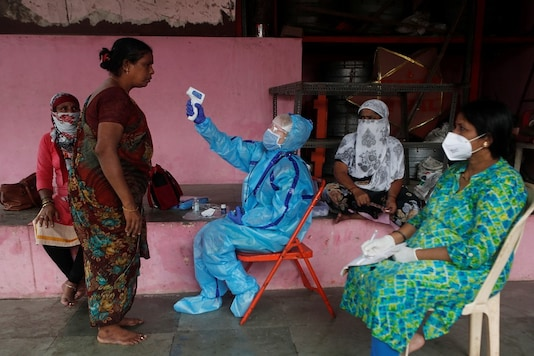 A health worker in personal protective equipment (PPE) checks the temperature of a resident with an electronic thermometer during a check up campaign for the coronavirus disease (COVID-19). (Reuters)