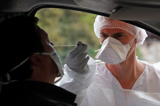 A nurse, wearing protective suit and face mask, administers a nasal swab to a patient at a drive-through testing site for coronavirus disease (COVID-19) near the hospital in Laval, in Mayenne department, France, July 15, 2020. REUTERS/Stephane Mahe