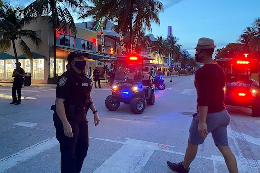 Police officers maintain the 8 pm curfew, imposed due to Florida's climbing numbers of coronavirus disease (COVID-19) cases, in Miami Beach, Florida, U.S. July 18, 2020.  REUTERS/Liza Feria