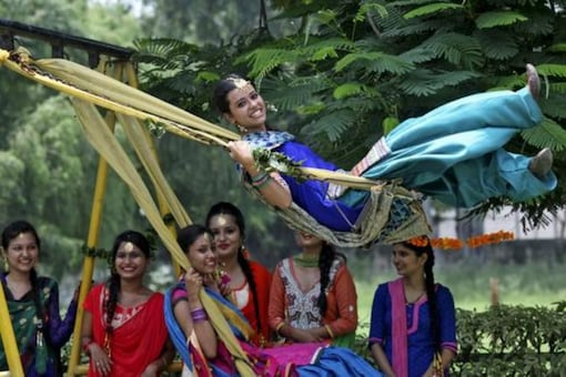 Traditionally dressed girls play on swings... Traditionally dressed girls play on swings during the Teej festival in Chandigarh. (Image courtesy: Reuters)