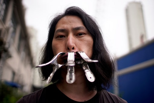 Brother Nut, Chinese performance artist with three metallic clips sealing his mouth, poses for a picture in Shanghai, following the COVID-19 outbreak, China July 13, 2020. Picture taken July 13, 2020. REUTERS/Aly Song