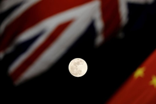 The super blue moon is seen between British and Chinese flags raised at Tiananmen square in Beijing as British Prime Minister Theresa May visit China's capital, January 31, 2018. REUTERS/Damir Sagolj
