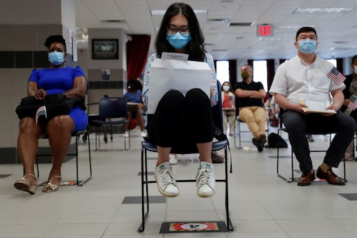 Citizen candidates sit socially distanced and wearing protective face masks, as the outbreak of the coronavirus disease (COVID-19) continues, during a U.S. Citizenship and Immigration Services (USCIS) naturalization ceremony in New York City, New York, U.S., July 22, 2020. REUTERS/Shannon Stapleton