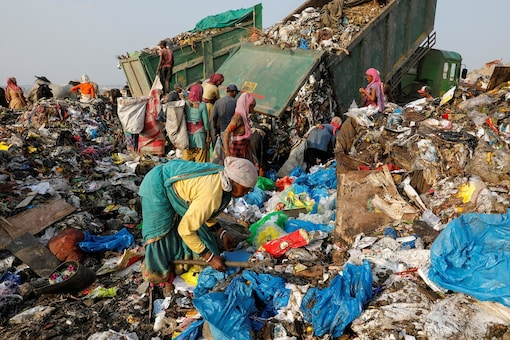 Waste collectors look for recyclable materials near bags of disposed medical waste at a landfill site, during the coronavirus disease (COVID-19) outbreak, in New Delhi, India, July 9, 2020. REUTERS/Adnan Abidi