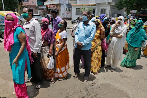 People wearing masks as a precaution against the coronavirus stand in a queue out side a bank in Ahmedabad, India, Monday. (AP Photo/Ajit Solanki)