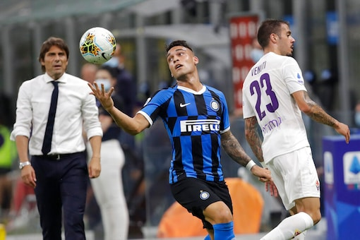 Inter Milan's Lautaro Martinez, center, holds the ball during a Serie A soccer match between Inter Milan and Fiorentina, at the San Siro stadium in Milan, Italy, Wednesday, July 22, 2020. (AP Photo/Luca Bruno)