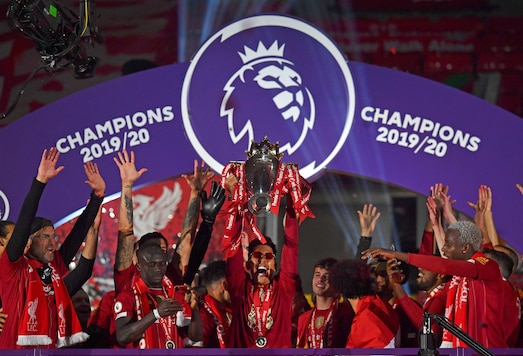 Liverpool's Roberto Firmino holds the English Premier League trophy aloft after it was presented following the Premier League soccer match between Liverpool and Chelsea at Anfield stadium in Liverpool, England, Wednesday, July 22, 2020. (Paul Ellis, Pool via AP)