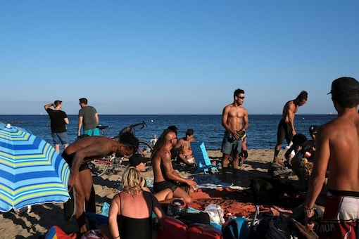 FILE PHOTO: People enjoy the sunny weather at Barceloneta beach, after Catalonia's regional authorities and the city council announced restrictions to contain the spread of the coronavirus disease (COVID-19) in Barcelona, Spain July 19, 2020. REUTERS/Nacho Doce