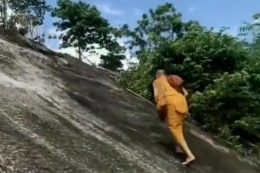 Monk climbs up the mountain with ropes. Credits: Twitter