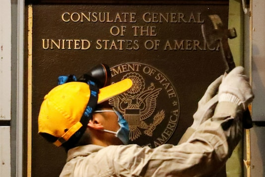 A worker removes an insignia at the US Consulate in Chengdu, China. (Reuters)