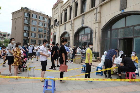Residents wearing face masks line up to receive nucleic acid tests after new cases of coronavirus disease (COVID-19) were confirmed in Dalian, Liaoning province, China July 26, 2020. cnsphoto via REUTERS. ATTENTION EDITORS - THIS IMAGE WAS PROVIDED BY A THIRD PARTY. CHINA OUT.