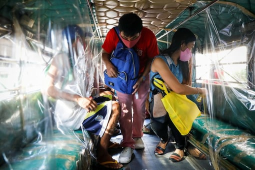 A passenger wearing a mask for protection against the coronavirus disease (COVID-19) boards the jeepney, while another sprays disinfectant on her seat, in Quezon City, Metro Manila, Philippines. (Image: Reuters)