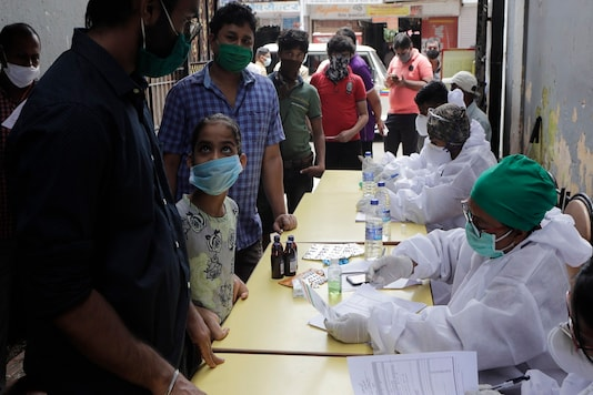 People wait in a queue for swab sample test for COVID-19  at medical camp in Mumbai.  (AP Photo/Rajanish Kakade)