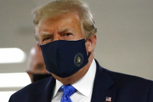 File photo of President Donald Trump wearing a mask as he walks down the hallway during his visit to Walter Reed National Military Medical Center in Bethesda. (Image: AP)