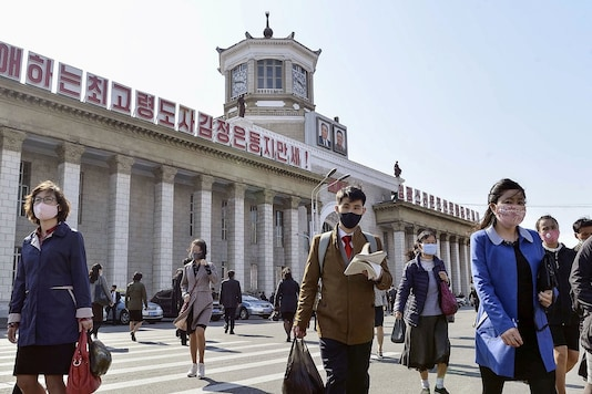 People wearing protective face masks walk amid concerns over the new coronavirus disease (COVID-19) in front of Pyongyang Station in Pyongyang, North Korea April 27, 2020, in this photo released by Kyodo. Mandatory credit Kyodo/via REUTERS