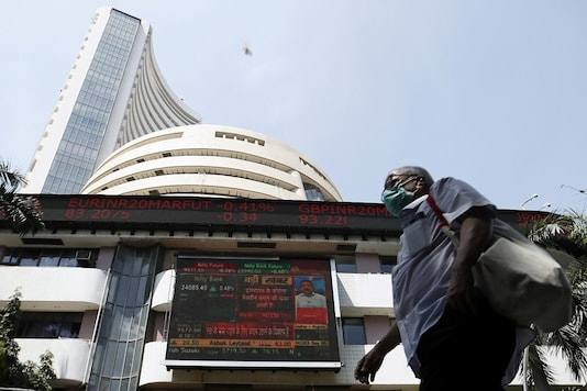 FILE PHOTO:  A man wearing a protective mask walks past the Bombay Stock Exchange (BSE) building in Mumbai. REUTERS/Francis Mascarenhas/File photo