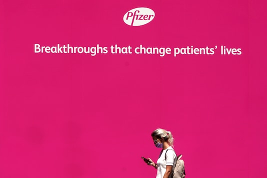 A woman walks past a sign outside Pfizer Headquarters in the Manhattan borough of New York City. (Reuters)