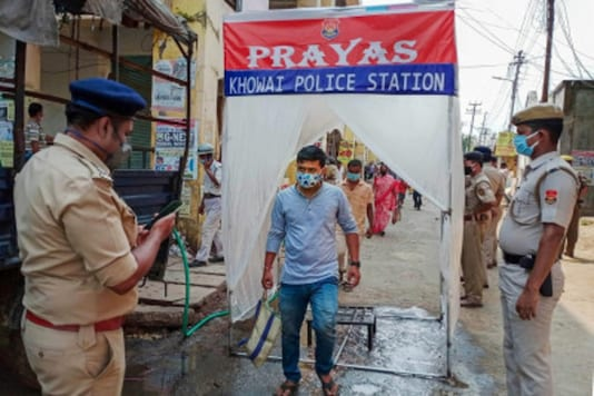 A man steps out of a body sanitizing tunnel at the entrance of a market, installed by Khowai police in Khowai district, Tripura. (PTI)