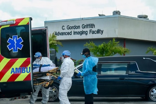 FILE PHOTO: Emergency Medical Technicians (EMT) arrive with a patient while a funeral car begins to depart at North Shore Medical Center where the coronavirus disease (COVID-19) patients are treated, in Miami, Florida, US July 14, 2020. (REUTERS/Maria Alejandra Cardona)