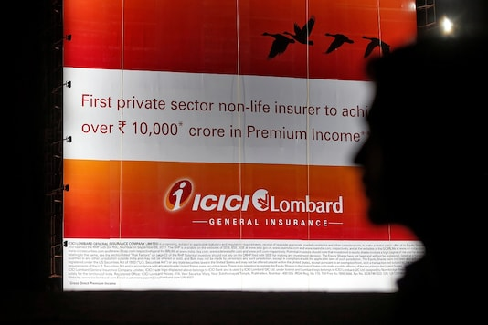 (For representation) A man walks past a billboard of Indian insurer ICICI Lombard in Mumbai.  REUTERS/Shailesh Andrade - RC15831CAA30
