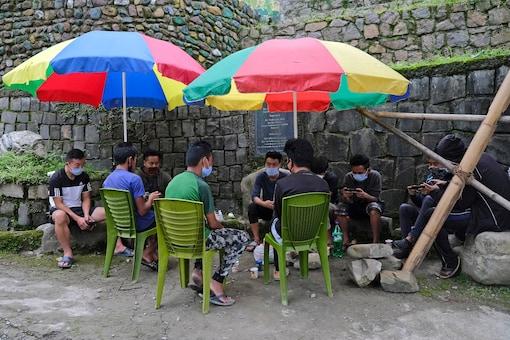 Men wearing face masks sit vigil at a gate erected to check the entry of non-residents into Kohima village.  (AP Photo/Yirmiyan Arthur)