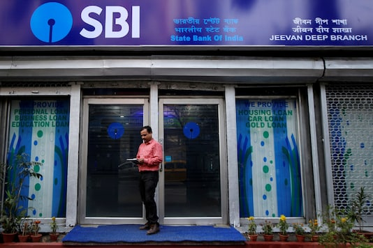 A man checks his mobile phones in front of State Bank of India (SBI) branch in Kolkata. (Reuters)