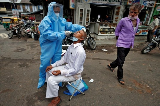 A healthcare worker wearing personal protective equipment (PPE) takes a swab from a man to test him for the coronavirus disease (COVID-19) in a street in Ahmedabad, India, July 7, 2020. (REUTERS/Amit Dave/Files)